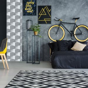 Grey multifunctional room with bed, desk, chair and wall decoration